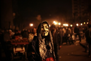 A protester in Tahrir Square wearing both a Guy Fawkes Mask and a Kufia